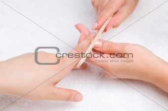 applying manicure with nail-file