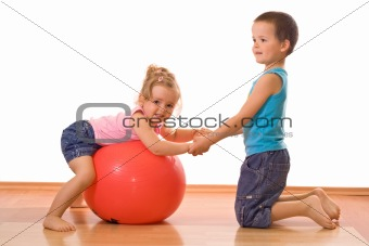 Little boy teaching her sister gymnastics