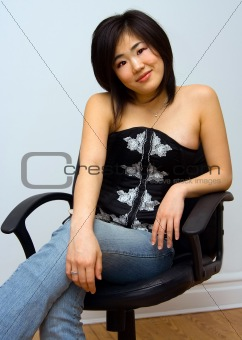 Beautiful Oriental woman sitting in chair