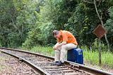 Man sitting on railroad track