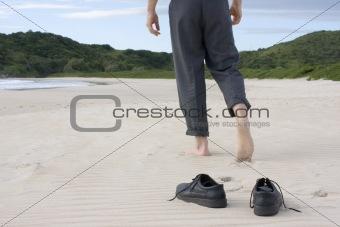 Businessman barefoot on beach