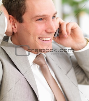 Young smiling business man using cell phone with hand behind hea
