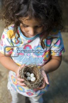 little girl holding nest with eggs