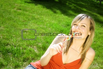 beautiful white woman with sugar candy smiling on a green grass