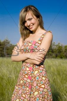 beautiful russian woman smiling in sun-dress on a grass field