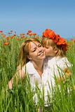 Little girl kissing her mother on the poppy field