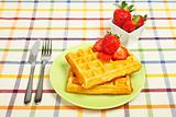 Waffles and strawberries on green plate