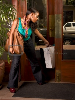 Black woman with shopping bag stuck in door (focus on bag)
