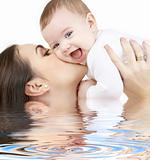 laughing baby playing with mother in water