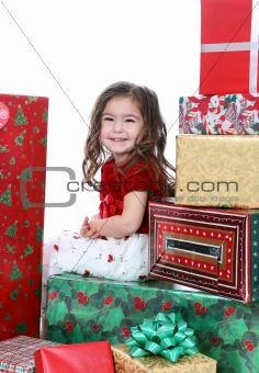 beautiful girl sitting in big pile of Christmas gifts