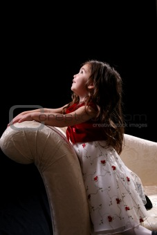 little girl kneeling on couch and looking up