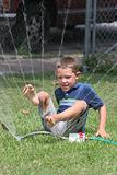 cute boy playing in sprinkler