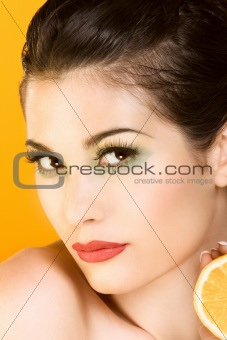 Beautiful woman with half of lemon looking at you