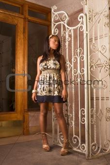 Black woman in denim dress standing by entrance
