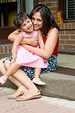 Mother and daughter sitting at the doorstep