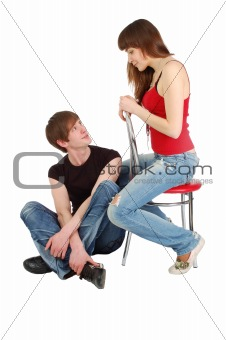 A pretty girl sitting on a chair discussing something with a guy