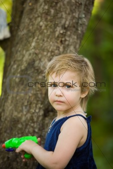 Little girl plays near a tree