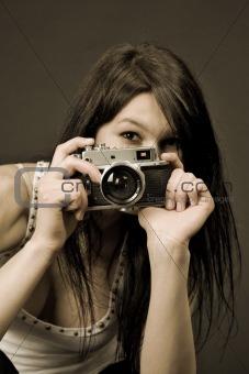 Beautiful photographer, focus on camera, sepia