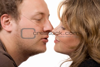 Portrait of young kissing couple. Isolated on white