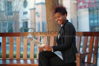 African American woman reading newspaper