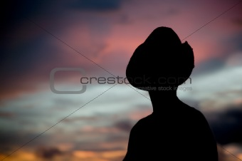 Woman in a cowboy hat silhouetted against a sunset sky.