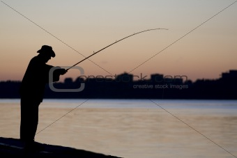 Fisherman fishing in the sun set