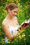 happy woman on a meadow with a book