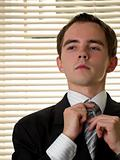 Yound businessman ties necktie