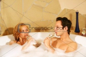 a couple is taking a bath with champagne in a glass