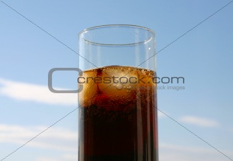 cola on ice, blue sky in background