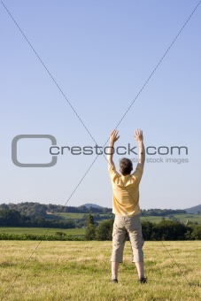 Man with uplifted arms in a meadow