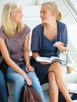 Happy young women sitting on steps