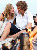 Young couple sitting together at beach by bonfire