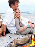 Happy young couple sitting by bonfire at beach in summer