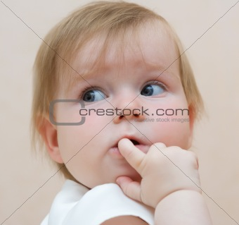 Baby with finger in mouth, looking backward
