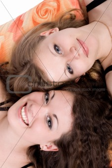 Portrait of the two beauty young women laying on a pillow 3