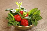 strawberry and mint leaves in bowl on burlap canvas background