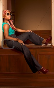 Urban African-American woman in jeans sitting