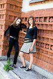 Two Young Women Near A Wall