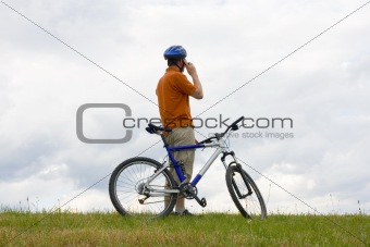 Man with mountain bike talking on cell phone