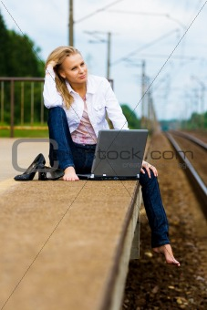 beautiful young lady with notebook waiting a train