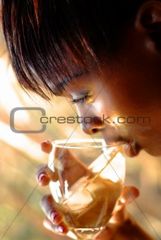 African woman sipping wine