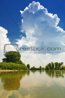 A cloud against a backdrop of blue sky. Landscape by the river